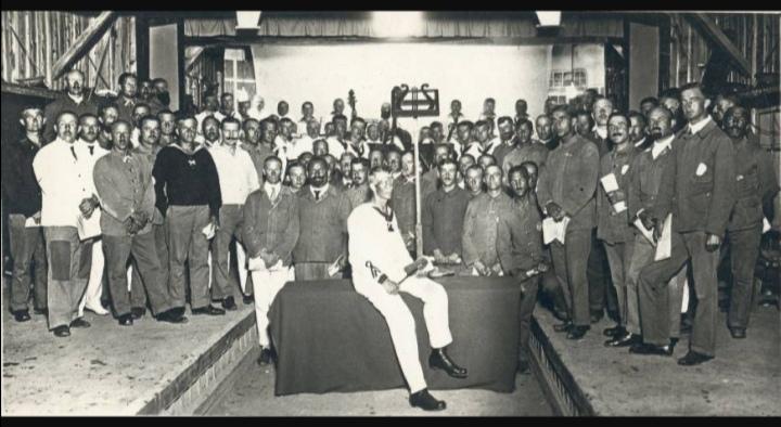 Le prisonnier de guerre Hermann Hansen, assis au centre, une chorale composée d'autres prisonniers de guerre et l'orchestre de Tokushima lors de la représentation de la Neuvième en juin 1918